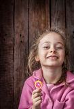 有棒棒糖的愉快的微笑的儿童女孩在土气木背景 免版税库存图片