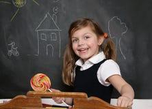 有棒棒糖的笑的女孩 免版税库存照片