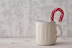 有棒棒糖的被编织的冬天杯子 免版税图库摄影