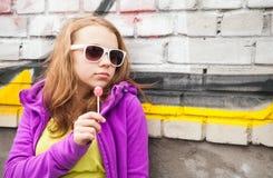 有棒棒糖的,垂直的室外画象白肤金发的女孩 免版税图库摄影