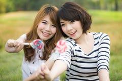 有棒棒糖的年轻愉快的妇女 库存图片