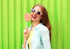 有棒棒糖的画象愉快的俏丽的微笑的妇女在五颜六色的绿色 免版税库存照片