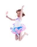 有棒棒糖跳的愉快的小女孩 免版税图库摄影