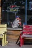 有棒球帽的一名妇女在酒吧喝并且冥想,沿高速公路24,中央科罗拉多 库存照片