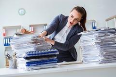 有棒球棒的恼怒的女实业家在办公室 库存照片