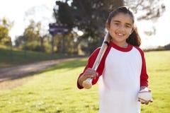 有棒球的年轻西班牙微笑对照相机的女孩和棒 库存照片
