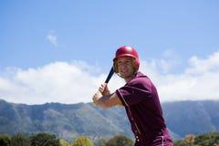 有棒的微笑的棒球运动员反对山 免版税图库摄影