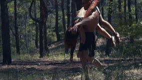 有棒的野蛮人在森林里在手中运载一名不自觉的妇女 股票录像