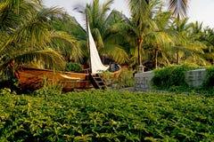 有棕榈庭院的小船 库存照片