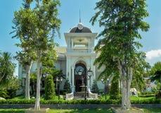 有棕榈树、树和风景设计的一个美丽的二层楼的房子在夏天 免版税库存图片