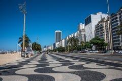 有棕榈树的全世界著名科帕卡巴纳散步,葡萄牙路面黑白马赛克在里约热内卢 免版税库存照片