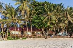 有棕榈的热带海滩前的平房 免版税库存照片
