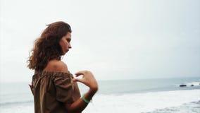 有棕色卷发的可爱的妇女站立在峭壁并且凝视海波浪 股票视频