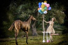 有棕色卷发的美丽的女孩在摆在微笑与五颜六色的气球和马的美妙的礼服犹特语在童话森林里 免版税库存图片