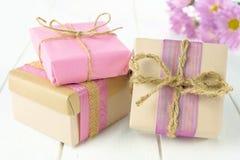 有棕色和桃红色包裹的礼物盒在白色木头 免版税库存照片