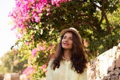 有棕色头发和米黄帽子的妇女在开花的bouga前面 库存照片