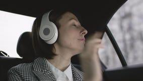 有棕色头发的俏丽的妇女在汽车的白色女衬衫和检查外套骑马和听与她的耳机的音乐 股票录像