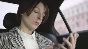 有棕色头发的俏丽的妇女在汽车的白色女衬衫和检查外套骑马和由她的电话的键入的消息 股票录像
