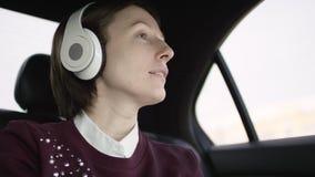 有棕色头发的俏丽的妇女在白色女衬衫和褐红的毛线衣在汽车的交通ridinging并且听与她的音乐 股票录像