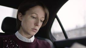 有棕色头发的俏丽的妇女在白色女衬衫和褐红的毛线衣骑马在汽车和讲话与她的电话 股票录像