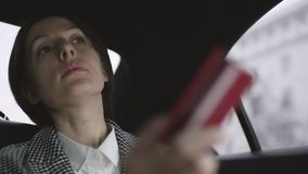 有棕色头发的妇女在汽车的白色女衬衫和检查外套骑马和要支付与卡片 股票录像