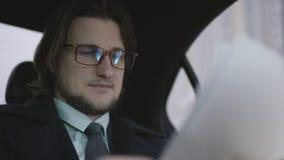 有棕色头发的帅哥在开心果衬衣和灰色外套和galsses骑马在汽车和检查文件与笔 股票录像