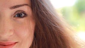 有棕色头发的画象半面孔特写镜头美丽的少妇微笑在一个大风天的 股票视频
