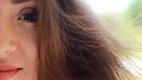 有棕色头发的画象半面孔特写镜头美丽的少妇微笑在一个大风天的 股票录像