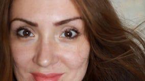 有棕色头发的画象特写镜头美丽的少妇微笑在一个大风天的 股票视频