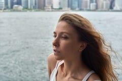 有棕色头发的美丽的女孩和在海洋的令人敬畏的眼睛在大都会香港靠岸 免版税图库摄影