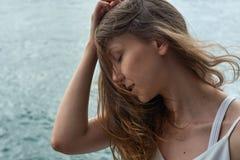 有棕色头发的美丽的女孩和在海洋的令人敬畏的眼睛在大都会香港靠岸 库存图片