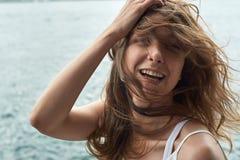 有棕色头发的美丽的女孩和在海洋的令人敬畏的眼睛在大都会香港靠岸 图库摄影