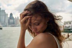有棕色头发的美丽的女孩在江边轻轻地微笑在大城市香港有多云天空背景 免版税库存图片