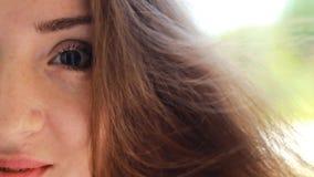 有棕色头发的美丽的少妇微笑在一个大风天的 画象半面孔特写镜头 影视素材