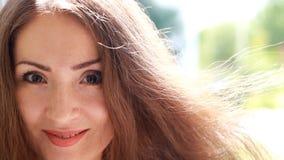 有棕色头发的美丽的少妇微笑在一个大风天的 画象女孩特写镜头 股票视频