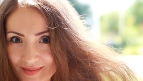 有棕色头发的美丽的少妇微笑在一个大风天的 画象特写镜头 股票视频