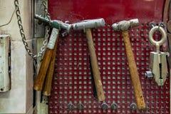 有棕色木把柄的四把老锤子和在墙壁上的钳位吊在木匠业工作的车间在红色背景 免版税图库摄影