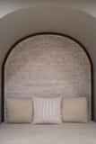 有棕色枕头和砖墙的布料沙发 图库摄影