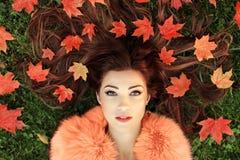 有棕色毛发的妇女倾斜的一个非常美丽的时兴的女孩 免版税图库摄影