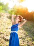 有棕色毛发的妇女的女孩摆在明亮的太阳的光芒的一个公园的一件蓝色礼服的 免版税图库摄影