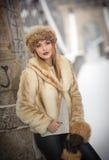 有棕色毛皮盖帽和夹克的可爱的妇女享受冬天的 摆在反对桥梁的时兴的白肤金发的女孩侧视图  免版税图库摄影