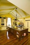 有棕色海岛的黄色木厨房 库存图片