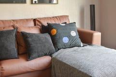 有棕色皮革沙发和黑枕头的现代客厅 免版税库存图片