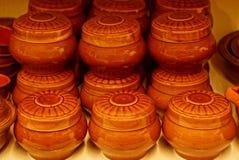 有棕色盖子的陶瓷罐在桌上 免版税库存照片
