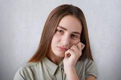 有棕色眼睛的一个相当女孩与充分的看一看哀伤的和保留她的在她的chee的嘴唇和长期平直的棕色头发手 免版税库存图片