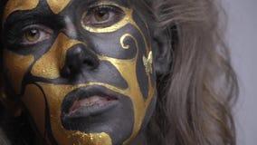 有棕色眼睛的一名妇女在黑色和金子艺术查寻并且看照相机,慢动作 影视素材