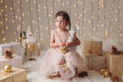有棕色眼睛的白种人儿童女孩坐与玩具庆祝圣诞节或新年的 库存照片