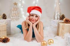 有棕色眼睛的白肤金发的白种人少妇在圣诞老人帽子庆祝圣诞节的 免版税图库摄影