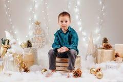 有棕色眼睛的英俊的白种人学龄前儿童男孩在绿色衬衣和牛仔裤庆祝圣诞节的 库存照片