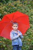 有棕色眼睛的英俊的逗人喜爱的男孩在一件牛仔裤夹克在有一把红色伞的秋天公园, 库存照片